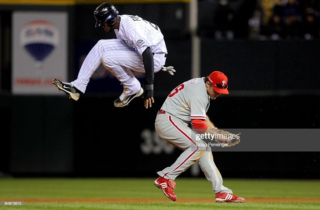 Dexter Fowler #24 of the Colorado Rockies hurdles safely over Chase Utley #26 the Philadelphia Phillies in Game Four of the NLDS during the 2009 MLB Playoffs at Coors Field on October 12, 2009 in Denver, Colorado.