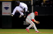Dexter Fowler of the Colorado Rockies hurdles safely over Chase Utley the Philadelphia Phillies in Game Four of the NLDS during the 2009 MLB Playoffs...