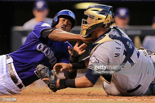 Dexter Fowler of the Colorado Rockies is tagged out by catcher Martin Maldonado of the Milwaukee Brewers as Fowler tried to score on a base hit by...