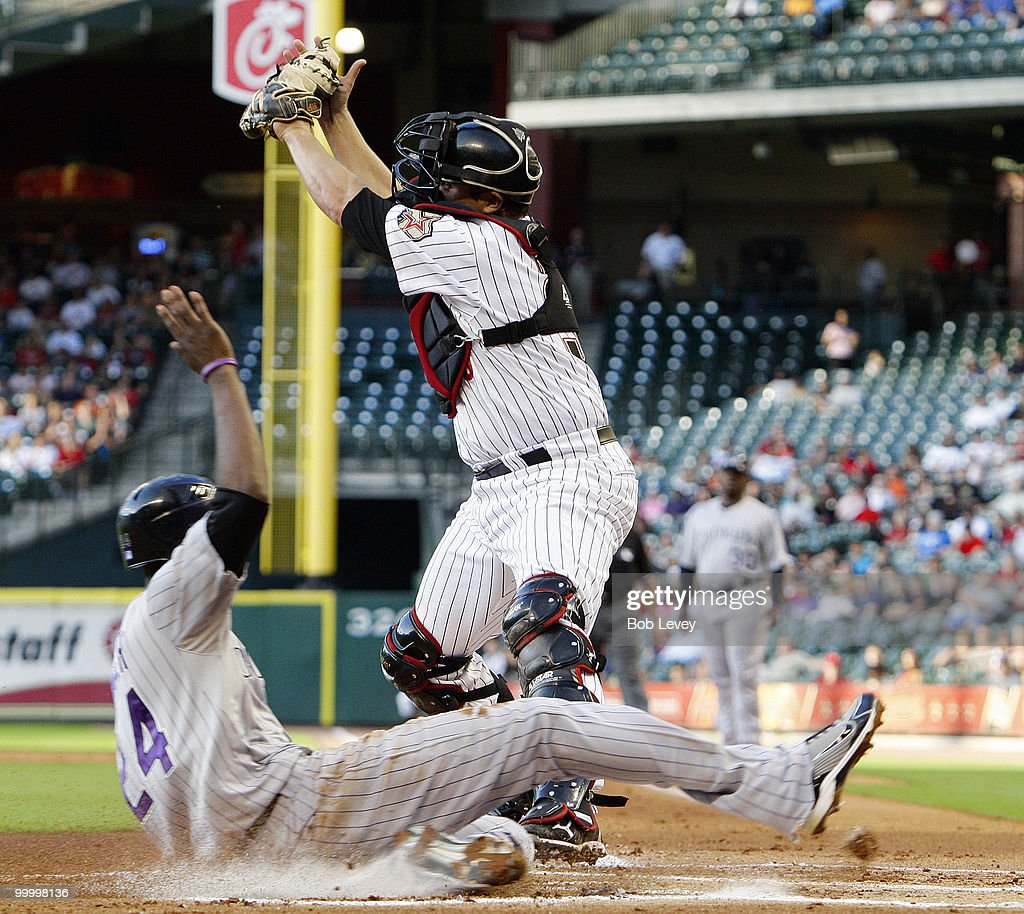 Dexter Fowler #24 of the Colorado Rockies scores in the first inning as catcher Kevin Cash #36 of the Houston Astros takes the high throw at Minute Maid Park on May 19, 2010 in Houston, Texas.