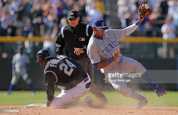 Dexter Fowler of the Colorado Rockies slides into second safely with the game winning hit as shortstop Starlin Castro of the Chicago Cubs takes the...
