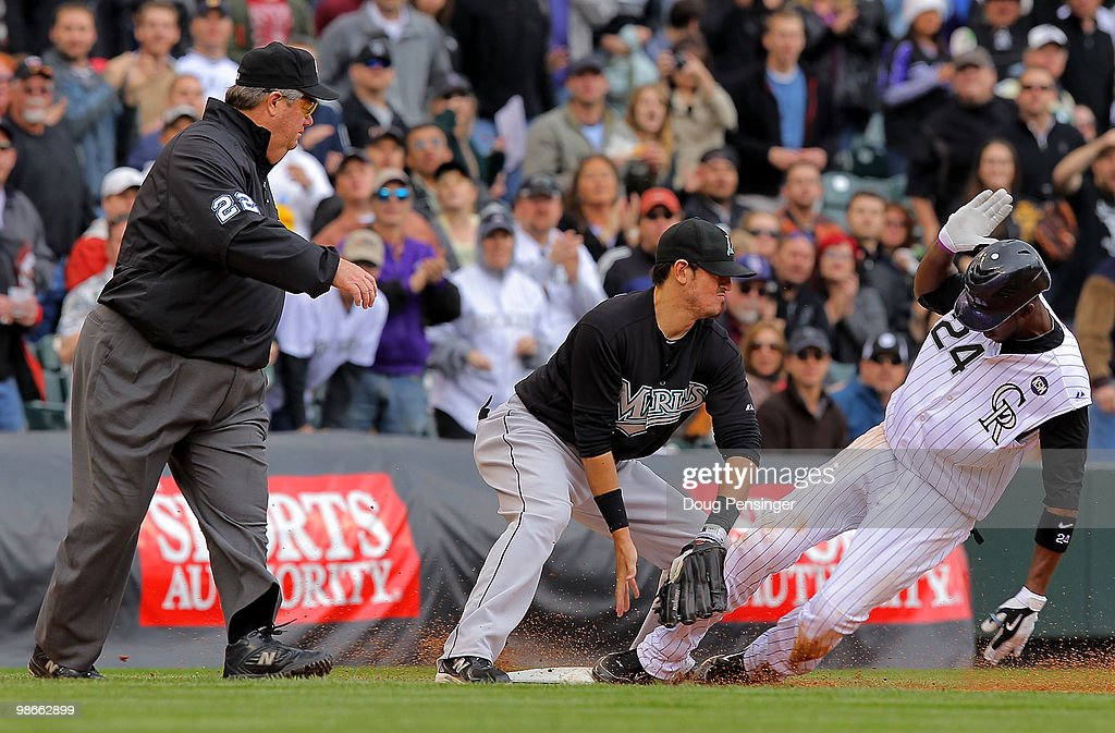 Dexter Fowler of the Colorado Rockies slides into third with an RBI triple as third baseman Jorge Cantu of the Florida Marlins is unable to handle...