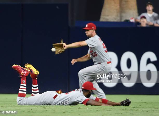 Dexter Fowler of the St Louis Cardinals dives but can't make the catch on a single hit by Clayton Richard of the San Diego Padres as Stephen Piscotty...