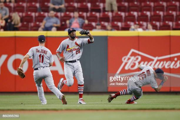 Dexter Fowler of the St Louis Cardinals makes a catch between Paul DeJong and Kolten Wong in the seventh inning of a game against the Cincinnati Reds...