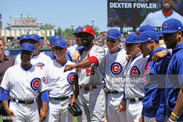 Dexter Fowler of the St Louis Cardinals poses with members of the Chicago Cubs after receiving his World Series ring before a game at Wrigley Field...