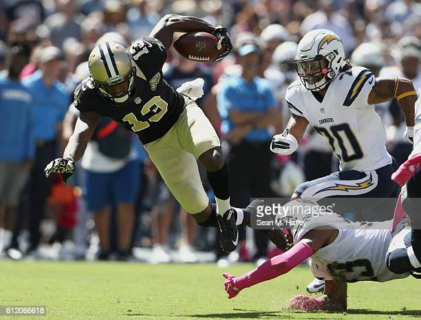 Dexter McCoil of the San Diego Chargers trips up Michael Thomas of the New Orleans Saints as Dwight Lowery of the San Diego Chargers pursues in the...