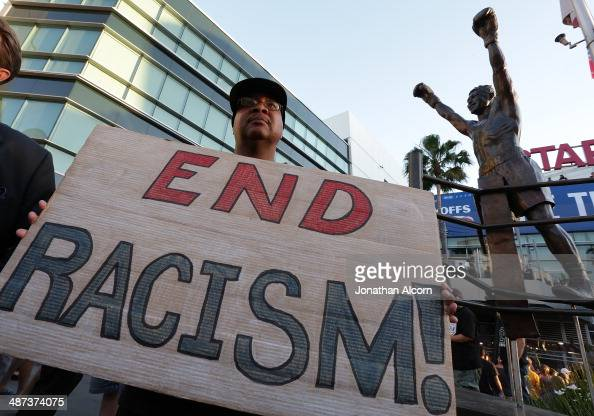 Dexter McLeod holds a sign protesting racist comments made by LA Clippers owner Donald Sterling outside Staples Center before a playoff game on April...
