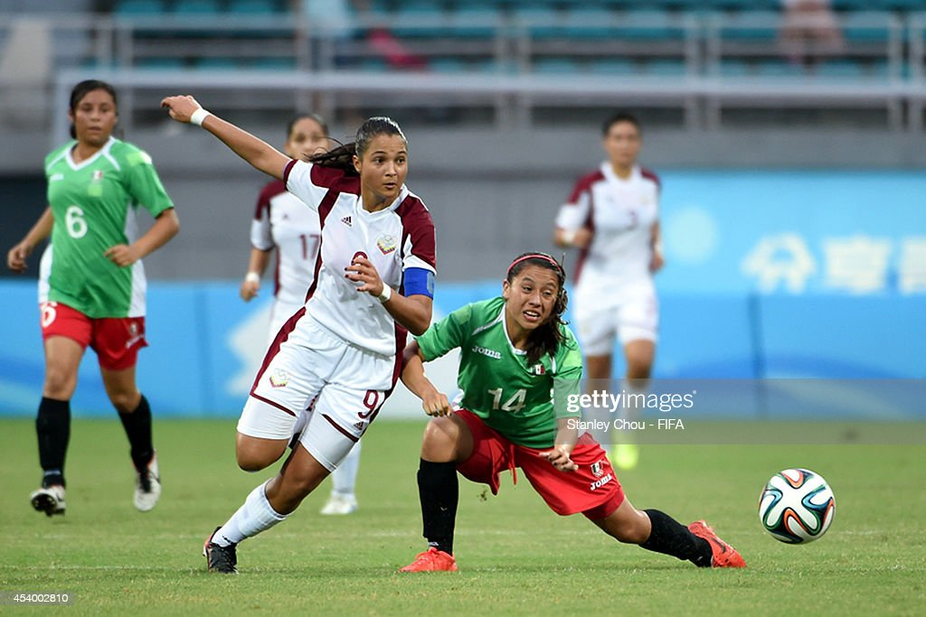 Deyna Castellanos of Venezuela competes with Duice Martinez of Mexico during the 2014 FIFA Girls Summer Youth Olympic Football Tournament Semi Final match between Venezuela and Mexico at Wutaishan Stadium on August 23, 2014 in Nanjing, China.