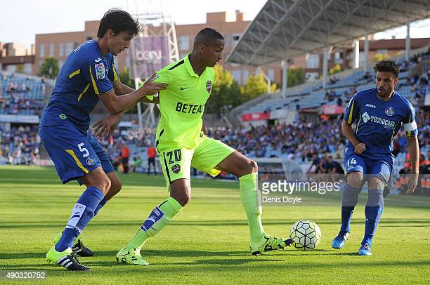 Deyverson of Levante is tackled by Santiago Vergini and Pedro Leon of Getafe during the La liga match between Getafe and Levante at estadio Coliseum...