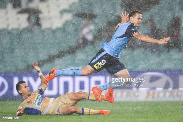 Deyvison Rogério da Silva Bobô of the Sydney FC goes flying over Jets Daniel Georgievski in the pouring rain during the round seven ALeague match...