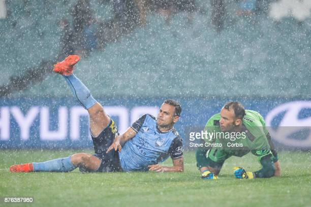 Deyvison Rogério da Silva Bobô of the Sydney FC lands next to Jets goalkeeper Jack Duncan in the pouring rain during the round seven ALeague match...