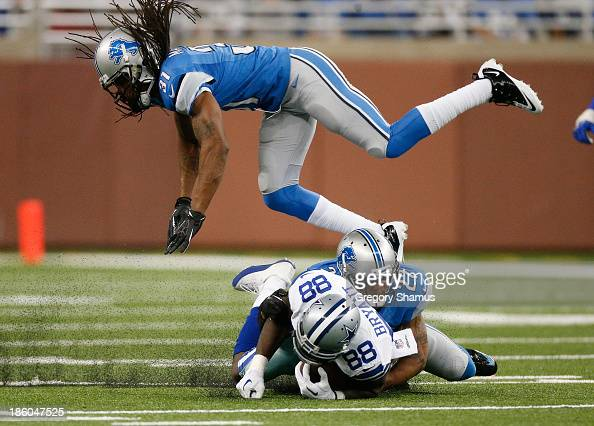 Dez Bryant of the Dallas Cowboys is tackled after a third quarter catch by Glover Quin and Rashean Mathis of the Detroit Lions at Ford Field on...
