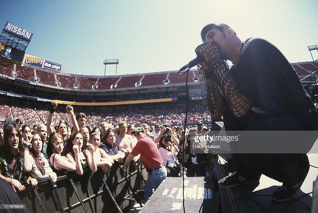 Dez Fafara, singer with US nu metal band Coal Chamber, singing into a microphone on stage in front of a crowd of fans during a live concert performance, United States, 1997.