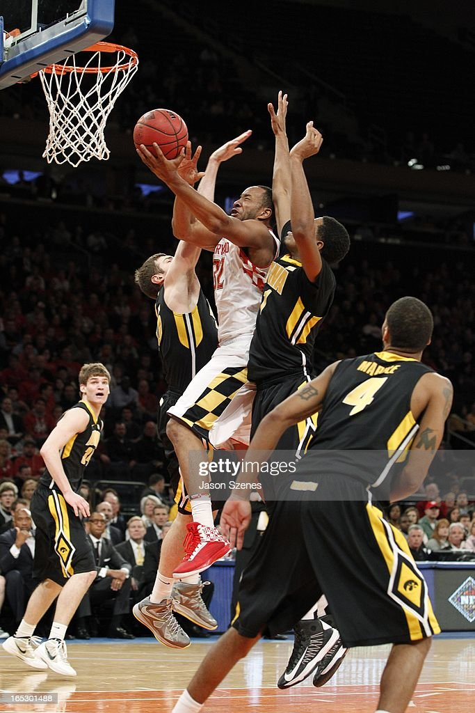 Dez Wells #32 of the Maryland Terapins puts up a shot past Melsahn Basabe #1 and teammate Eric May #25 of the Iowa Hawkeyes in the first half during the 2013 NIT Championship - Semifinals at the Madison Square Garden on April 2, 2013 in New York City.