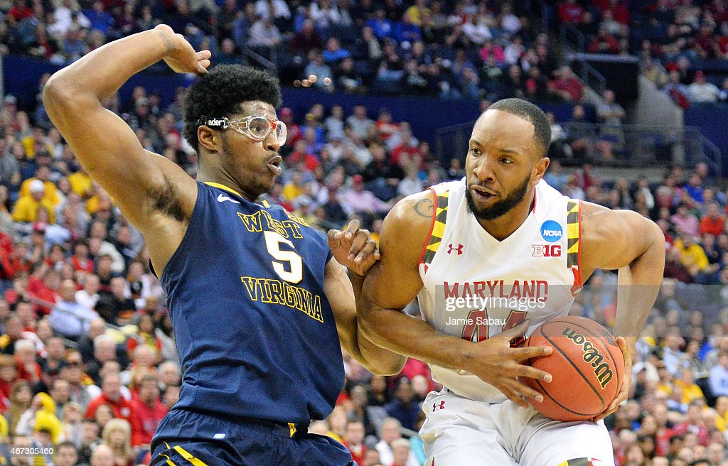 Dez Wells of the Maryland Terrapins drives against Devin Williams of the West Virginia Mountaineers in the first half during the third round of the...