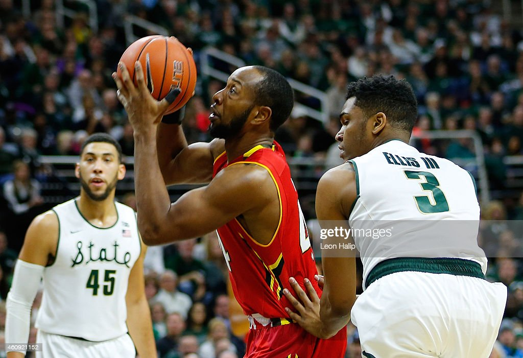 Dez Wells of the Maryland Terrapins drives the ball to the basket as Denzel Valentine and Alvin Ellis III of the Michigan State Spartans defend...