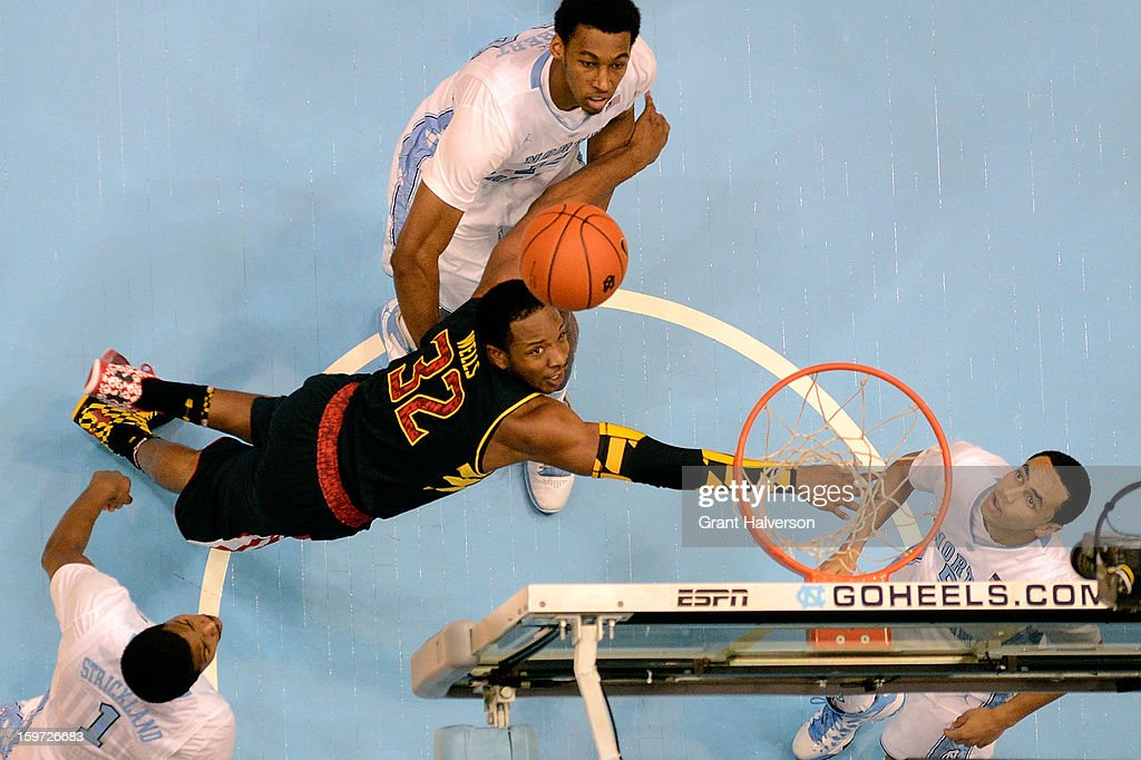 Dez Wells #32 of the Maryland Terrapins goes to the floor as he shoots against Dexter Strickland #1, Desmond Hubert #14 and Marcus Paige #5 of the North Carolina Tar Heels during play at the Dean Smith Center on January 19, 2013 in Chapel Hill, North Carolina. North Carolina won 62-52.