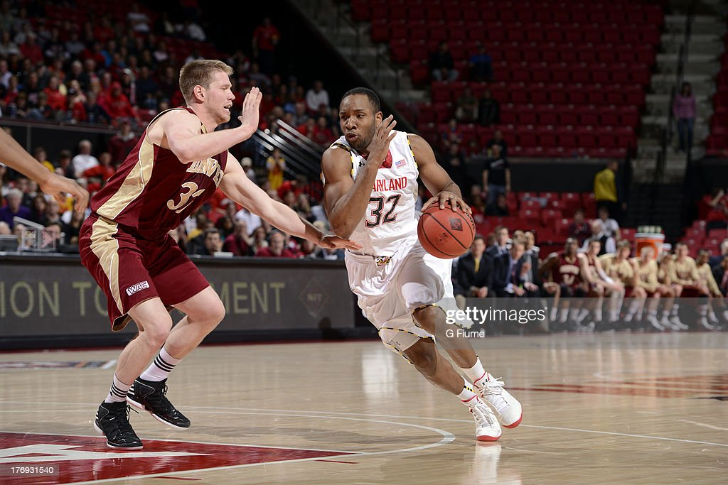 Dez Wells of the Maryland Terrapins handles the ball against Chase Hallam of the Denver Pioneers during the second round of the NIT Basketball...