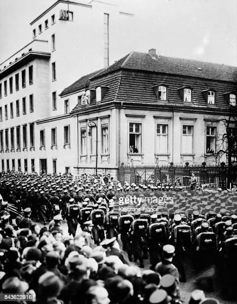 Défilé des troupes nazies devant le Führer qui les saluent debout dans sa voiture devant l'ancienne Chancellerie d'Etat à Berlin Allemagne en janvier...