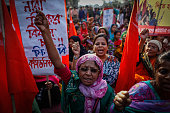 Women take part in the Bangladeshi Communist Party rally for International Women's Day holding flags and signs bearing the globally recognized...