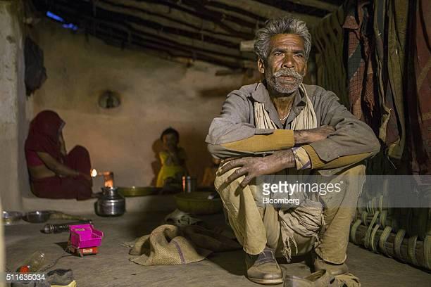 Dharmu Sahariya right sits with his family at his home in the village of Sakara in Lalitpur district Madhya Pradesh India on Saturday Feb 9 2016...