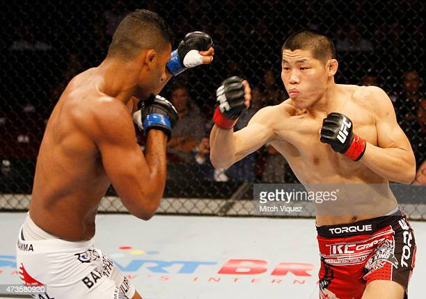 Dhiego Lima of Brazil and Li Jingling of China exchange punches in their welterweight fight during the UFC Fight Night event at the Mall of Asia...