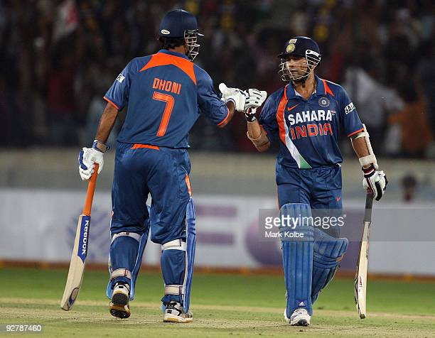 Dhoni and Sachin Tendulkar of India punch gloves during the fifth One Day International match between India and Australia at Rajiv Gandhi...
