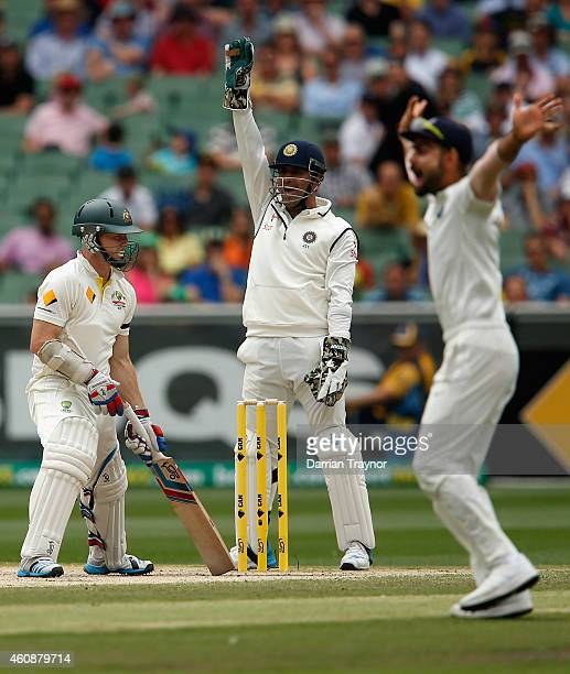 Dhoni and Virat Kohli of India appeal to the umpire for lbw as Chris Rogers of Australia looks on during day four of the Third Test match between...