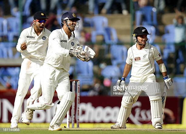 Dhoni and Virat Kohli of India celebrate after the dismissal of New Zealand batsman Kruger Van Wyk during third day of second Test match between...