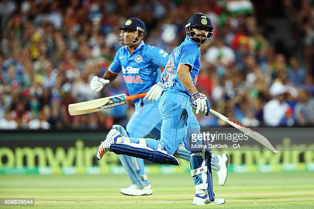 Dhoni and Virat Kohli of India runs between the wickets during game one of the Twenty20 International match between Australia and India at Adelaide...