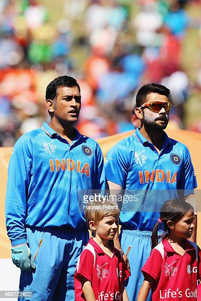 Dhoni of India and Virat Kohli of India sing the national anthem prior to the 2015 ICC Cricket World Cup match between Ireland and India at Seddon...