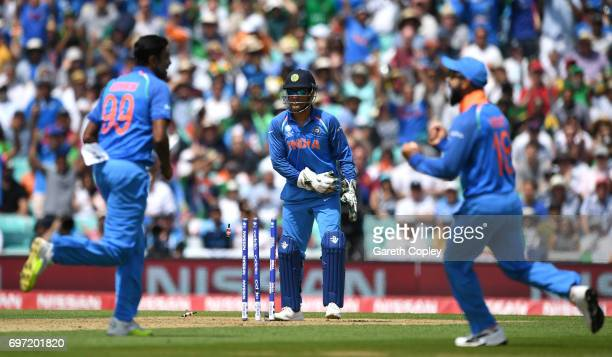 Dhoni of India breaks the stumps to run out Azhar Ali of Pakistan during the ICC Champions Trophy Final between India and Pakistan at The Kia Oval on...