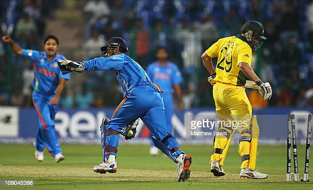 Dhoni of India celebrates stumping David Hussey of Australia off the bowling of Piyush Chawla during the 2011 ICC World Cup Warm up game between...