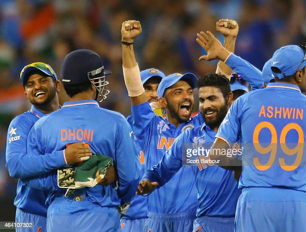 Dhoni of India celebrates with his teammates after running out AB de Villiers of South Africa during the 2015 ICC Cricket World Cup match between...