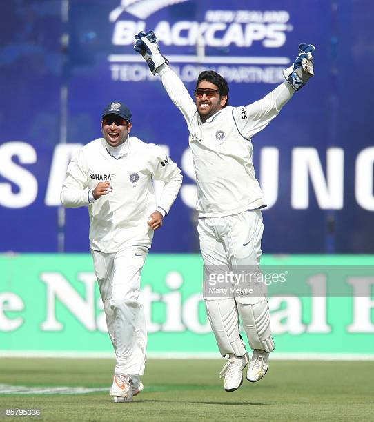 Dhoni of India celebrates with team mate VVS Laxman catching out Jesse Ryder of New Zealand during day two of the Third Test match between New...
