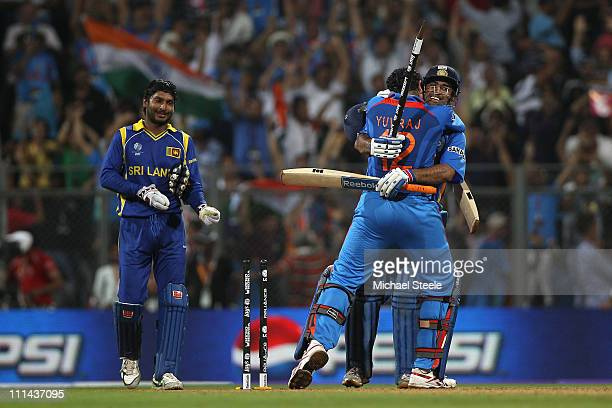 Dhoni of India celebrates with Yuvraj Singh after hitting a six to win by six wickets as Kumar Sangakkara captain of Sri Lanka looks on during the...