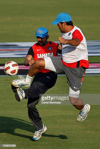 Dhoni of India challenges Gautam Gambhir for the ball during a warm up game of soccer at the Indian cricket team training session at Feroz Shah Kotla...