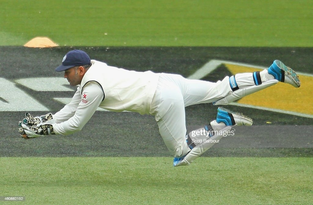 MS Dhoni of India dives to take a catch to dismiss Joe Burns of Australia during day four of the Third Test match between Australia and India at Melbourne Cricket Ground on December 29, 2014 in Melbourne, Australia..