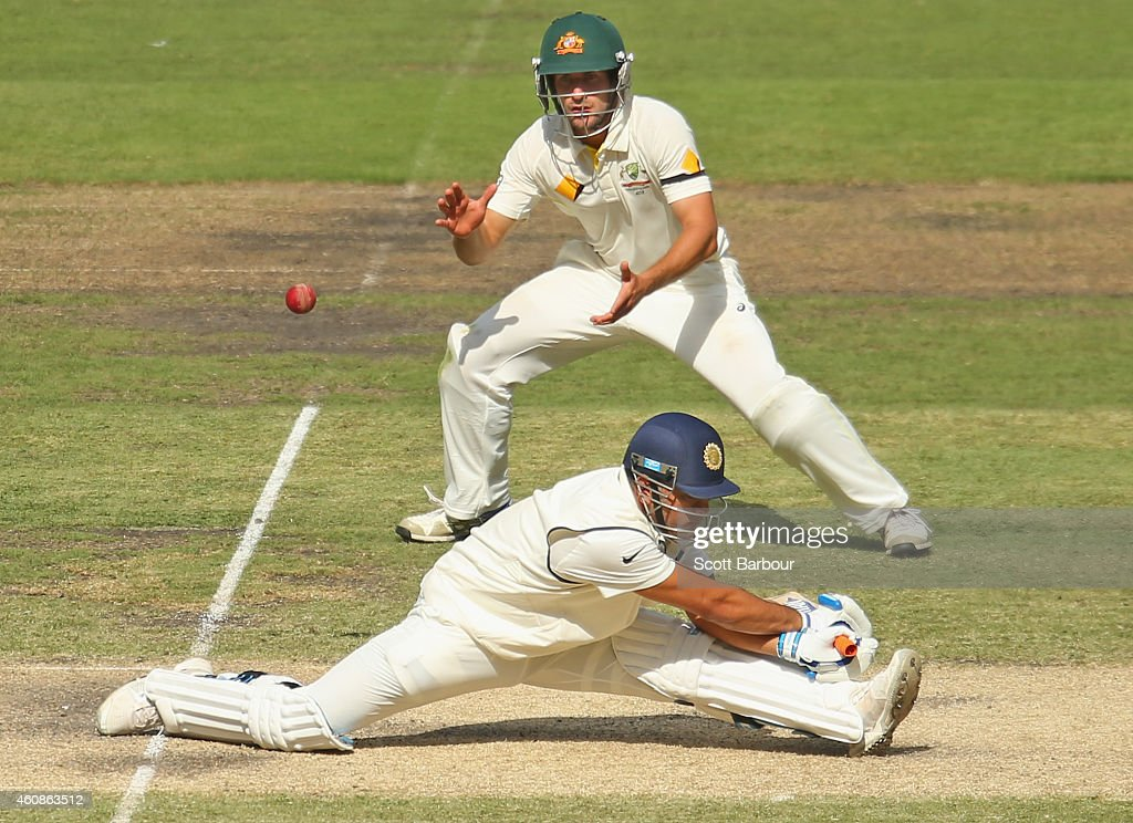 Dhoni of India slips as he plays a shot as Joe Burns of Australia looks on during day three of the Third Test match between Australia and India at...