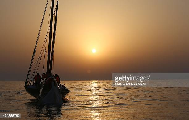 A dhow is seen at sunset during a training session on May 22 2015 in the waters off the island of Sir Bu Nair on the eve of the AlGaffal 60 feet...