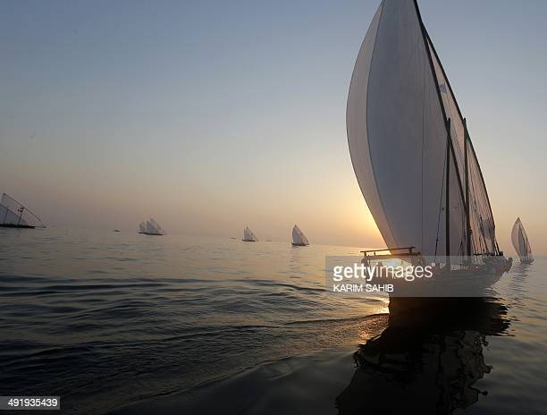 Dhows sail during the AlGaffal traditional longdistance dhow race towards the finish line as they race between the island of Sir Bu Nair near the...
