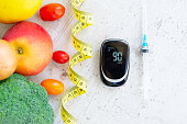 Diabetes healthy diet concept, raw vegetables with blood glucose meter and insulin syringe