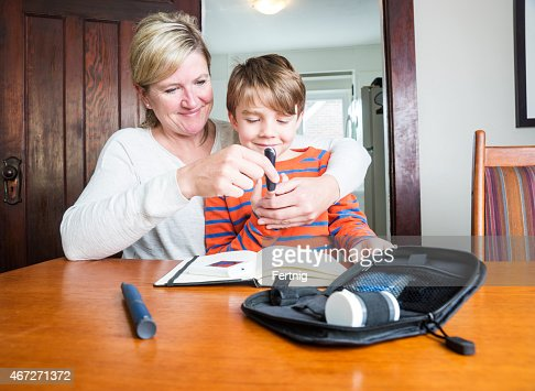 Diabetic child testing blood sugar with his mother