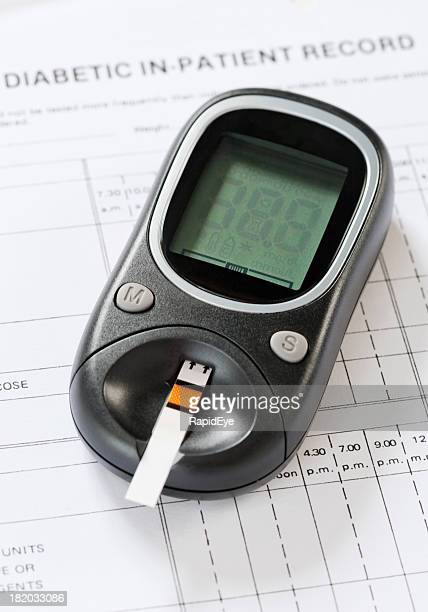 Diabetic glucometer with blood testing strip on medical form