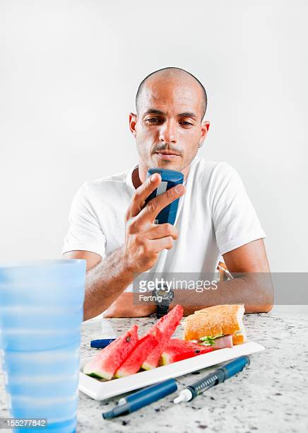 Diabetic Latino man checking his blood sugar