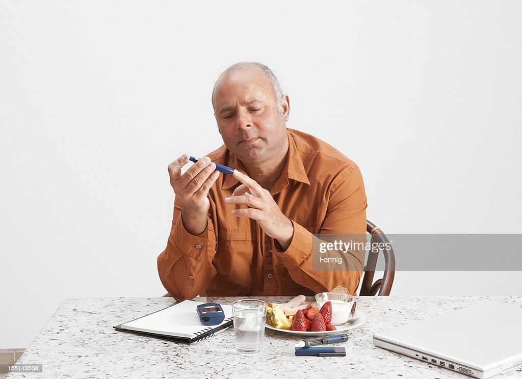 Diabetic man checking his blood sugar levels : Stock Photo