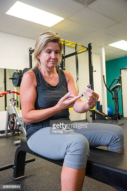Diabetic patient testing her blood sugar in a gym