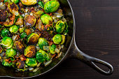 Diagonal Cast Iron Skillet with Brussels Sprouts over dark table top