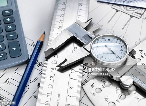 Dial caliper and engineering measurement equipment, sitting on technical drawing