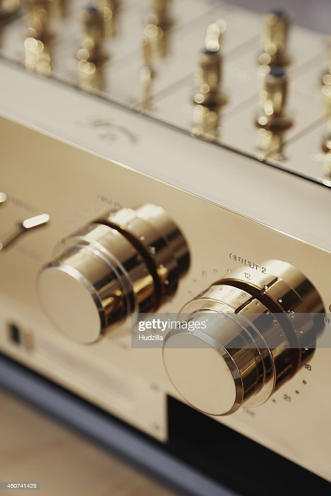 Dials on a gold color stereo, extreme close up
